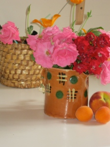 Photo shows vase of roses, apricots, basket.