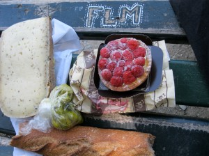 Picnic lunch displayed on a graffitied park bench in Limoges.