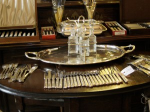 Photo shows display of silver tableware from a Paris antique shop.